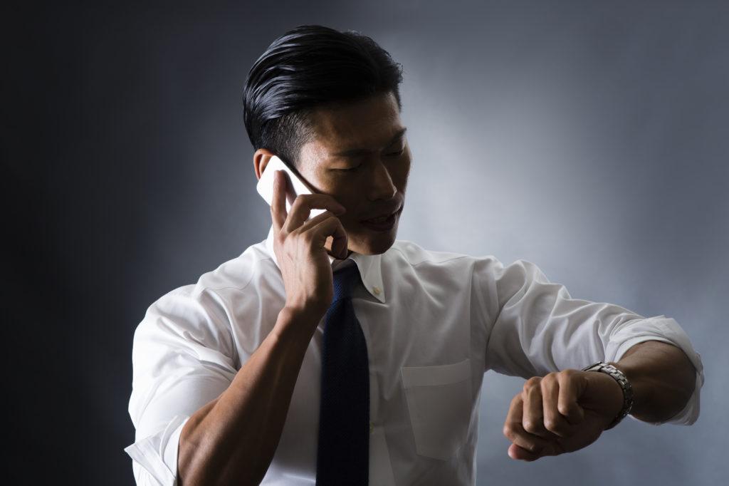腕まくりしたシャツを着て仕事する男性