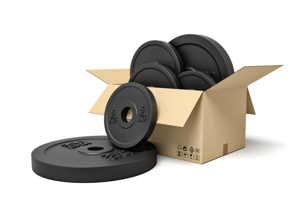 取り替え用の複数のダンベルプレートが箱から溢れ出す